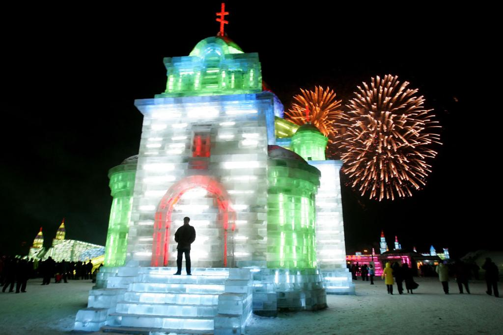 Fireworks are displayed as tourists visit the ice buildings on display at the Grand Ice and Snow World, part of the 23rd Harbin International Ice and Snow Festival.