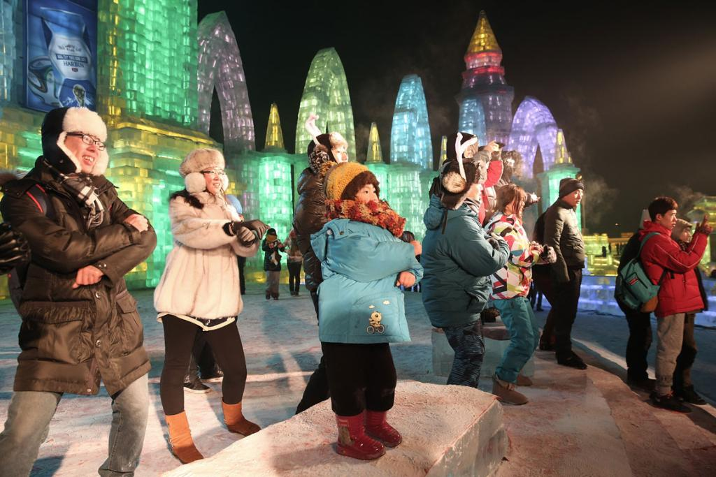 Tourists dance at the Grand Ice and Snow World during the 30th Harbin International Ice & Snow Sculpture Festival.