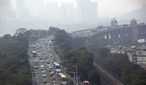 SMOG: Shrouded in haze, traffic moves along a bridge on the Chang Jiang river in Wuhan, China.