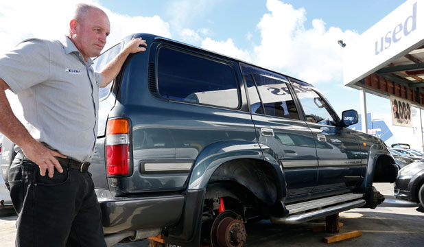 ANNOYED: Chris McQuade of the Car Company with a Toyota Landcruiser that had all four of its wheels stolen while the vehicle was in the car yard.