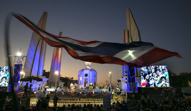 The Thai flag flies as thousands of protesters attend a rally at a democracy monument Sunday in Bangkok