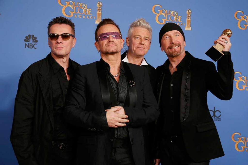 Adam Clayton, Bono, Larry Mullen, Jr., and The Edge (L to R), from the band U2, pose backstage with their award for Best Original Song for Ordinary Love from the film Mandela: Long Walk to Freedom.