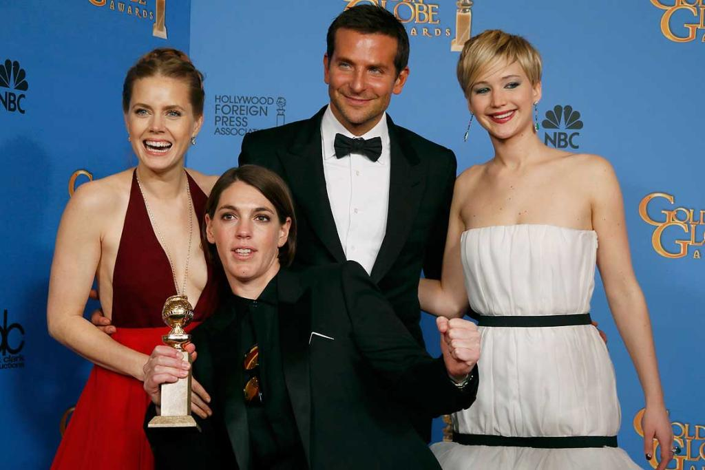 American Hustle stars Amy Adams (L), Bradley Cooper and Jennifer Lawrence (R) pose backstage with producer Megan Ellison after the film won the award for Best Motion Picture, Musical or Comedy.