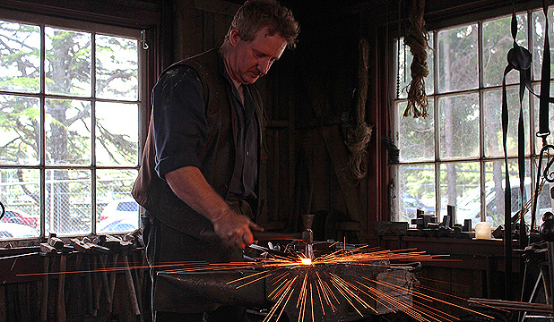 HOT STUFF: Blacksmith Richard Neville hammers out a fire poker in the darkness of his workshop at Motat.