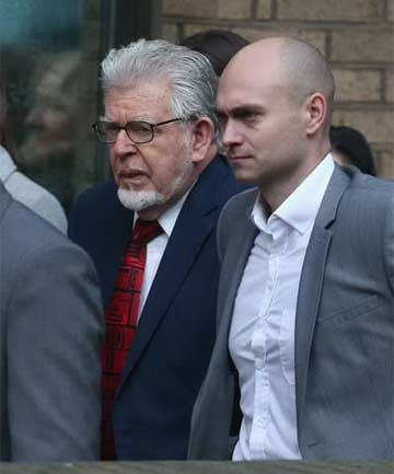 DENYING CHARGES: Entertainer Rolf Harris (left) arrives at Southwark Crown Court in London with security guards, before entering a not guilty plea on sexual assault charges.