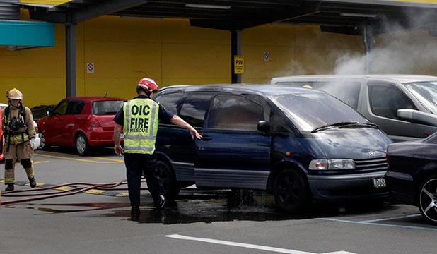UP IN FLAMES: Fire fighters put out the fire in the car after the children were removed.