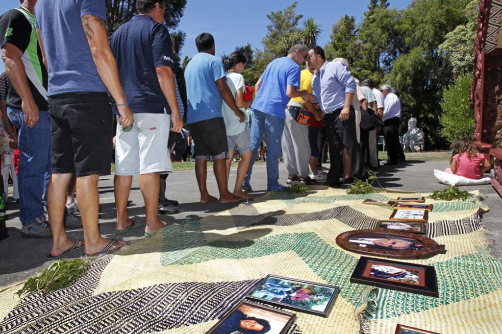 Photographs of members of the family who have passed away lie on a mat out side the wharenui.