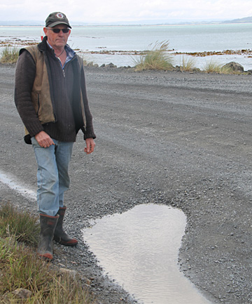 The Nuggets Rd resident Willy Simpson beside one of the larger potholes on the road.