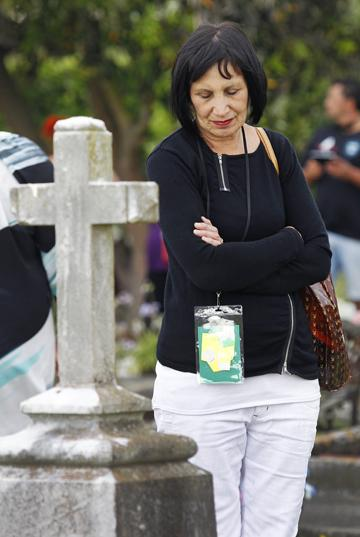 Yvonne Grant reads an inscription on one of the graves.