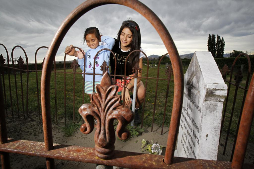 Peering into the past: Hineraukatauri Walker, 4, and cousin Summer Rose Malietoa look at one of their ancestor's graves at Maori Island urupa, a Maori burial site at Grovetow