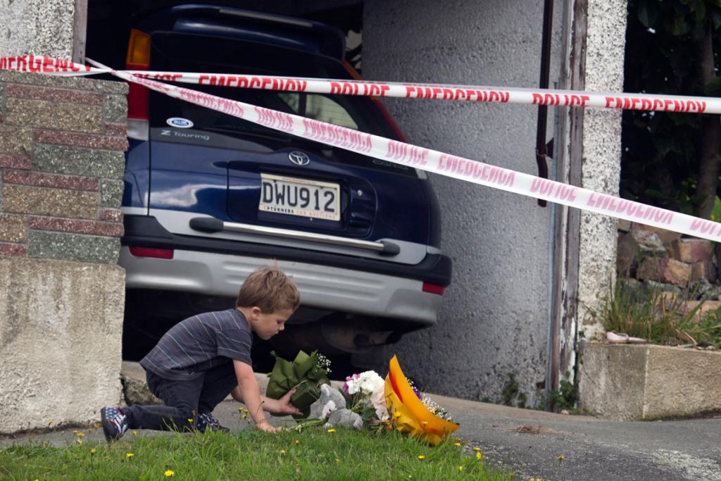 A young boy lays flowers by the house in Dunedin where two children and a man were killed in apparent murder-suicide.
