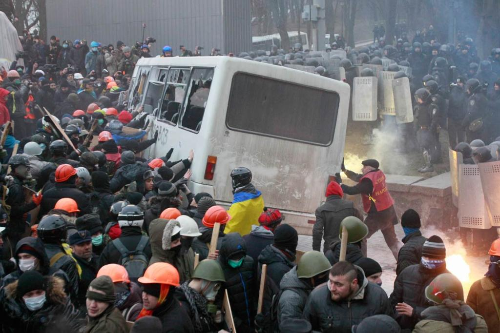 Pro-European integration protesters attack a police van during a rally near government administration buildings.