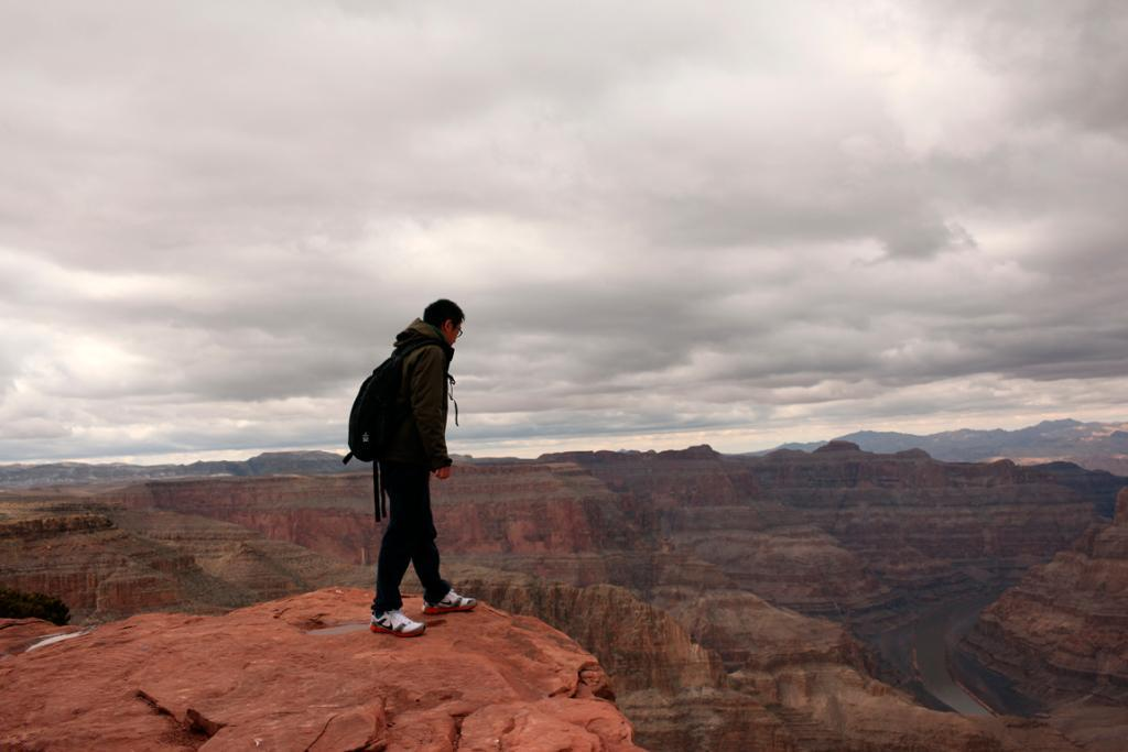 A tourist peers over a ledge overlooking the Grand Canyon and the Colorado River below, on the Hualapai Indian Reservation, Arizona. This steep, terraced formation carved by the Colorado River in Arizona shows millions of years of natural history.
