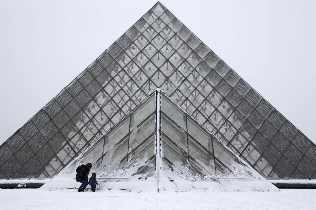A parent and child enjoy the snow in front of the Pyramid of the Louvre Museum in Paris. The world's most visited art gallery is home to thousands of masterpieces and considered a crowning glory of European civilisation.