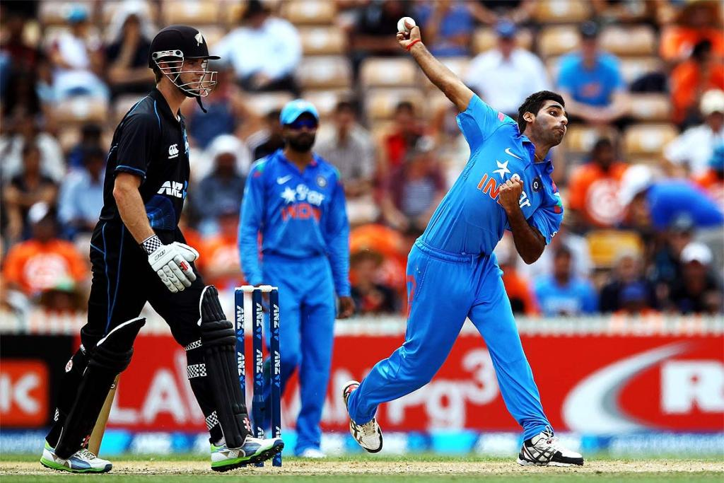 Bhuvneshwar Kumar of India bowls as Martin Guptill looks on.