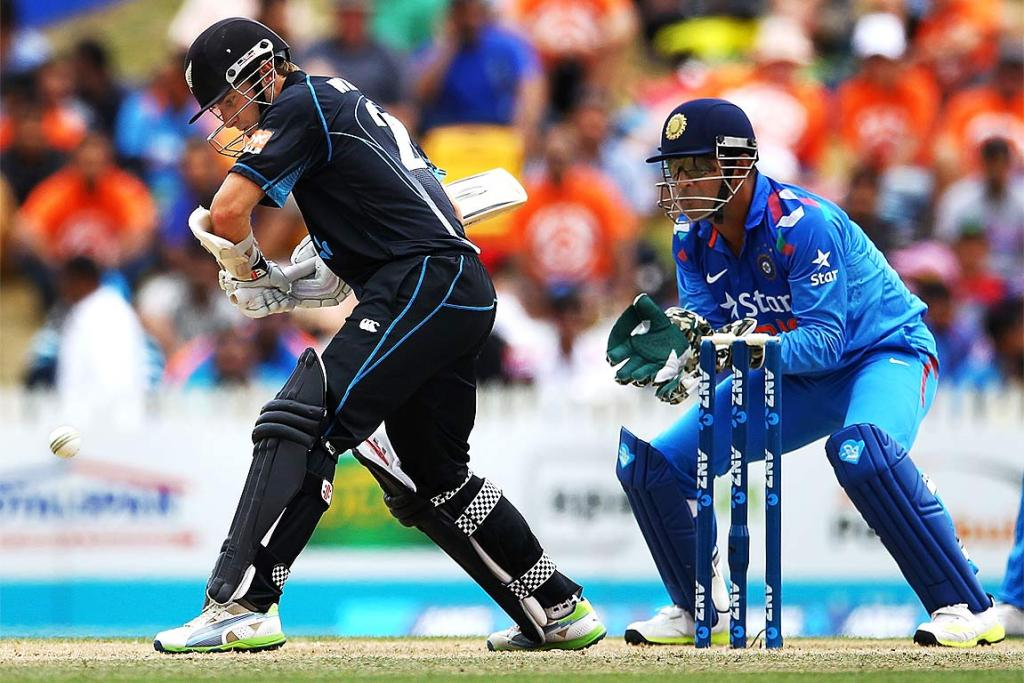 Kane Williamson of New Zealand bats as MS Dhoni of India looks on.