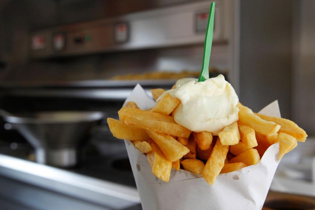 A large cone of fries with mayonnaise sauce is seen at Frit-Flagey, a popular frites stand in Brussels.