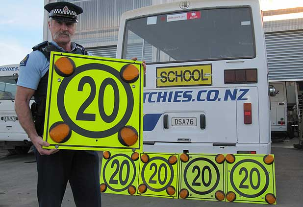 Constable Bruce Dow of the Oamaru police shows the slow down signs.