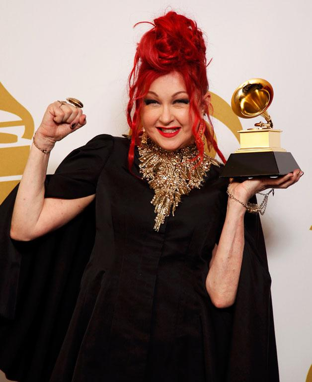 Musician Cyndi Lauper poses backstage with her award for best musical theater album for Kinky Boots.