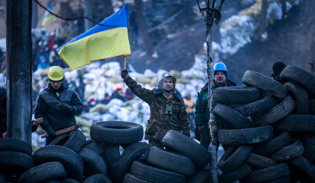 Anti-government protestors look towards police lines from a wall of tyres on Monday in Kiev.