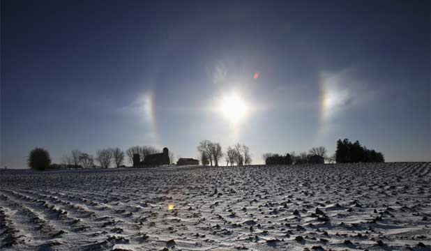 "ICY SUNRISE: A ""sun dog"" atmospheric phenomenon appears over a farm in southern Minnesota. The halo around the sun is caused by the refraction of sunlight by small ice crystal in the atmosphere."