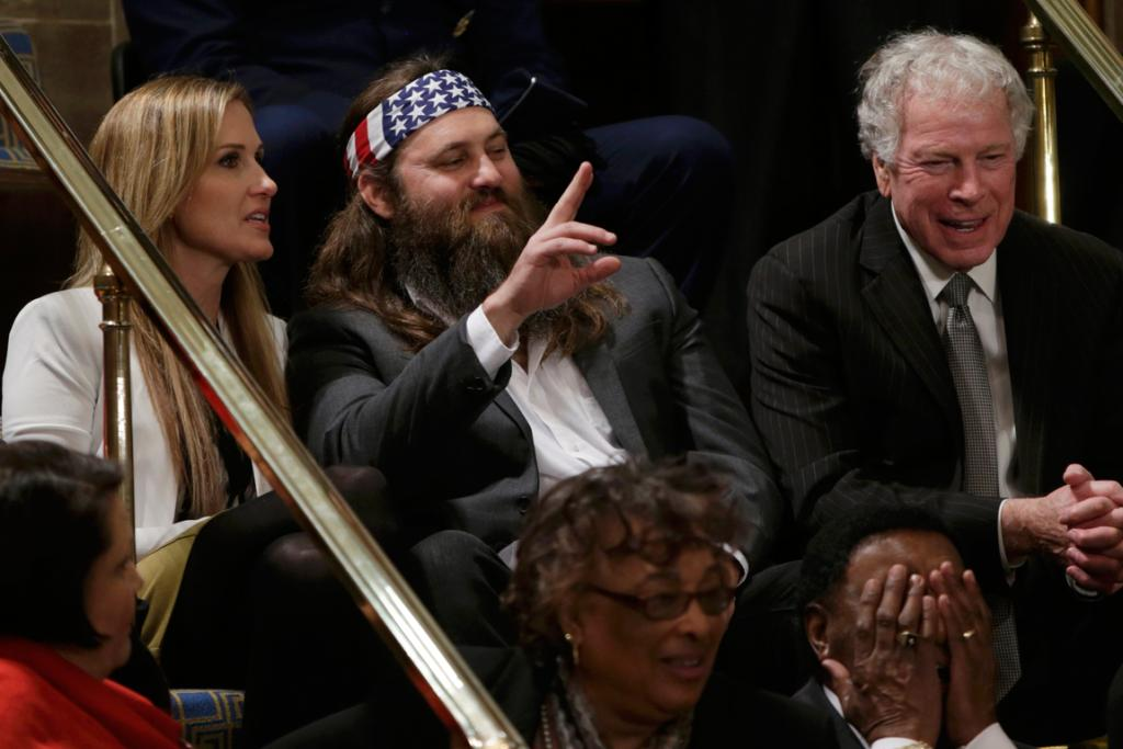 Duck Dynasty television show star Willie Robertson (centre) waves as he sits with his wife Korie (left) in the visitor's gallery of the US House of Representatives before the start of US President Barack Obama's State of the Union speech on Capitol Hill in Washington.