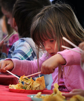 CULTURAL CELEBRATION: Katie Allison, 3, attempts to use chopsticks to eat the Chinese banquet at Waimataitai Kindergarten, to celebrate Chinese New Year.