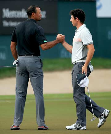HALFWAY THROUGH: Rory McIlroy (right) shakes hands with Tiger Woods. McIlroy leads at the halfway point of the Dubai Desert Classic by one shot.