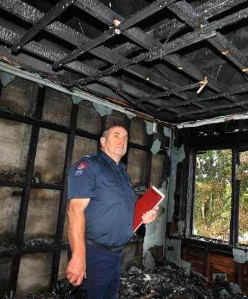 BLACKENED SHELL:   Southern region fire safety officer Stuart Ide investigates the gutted Lithgow St home.