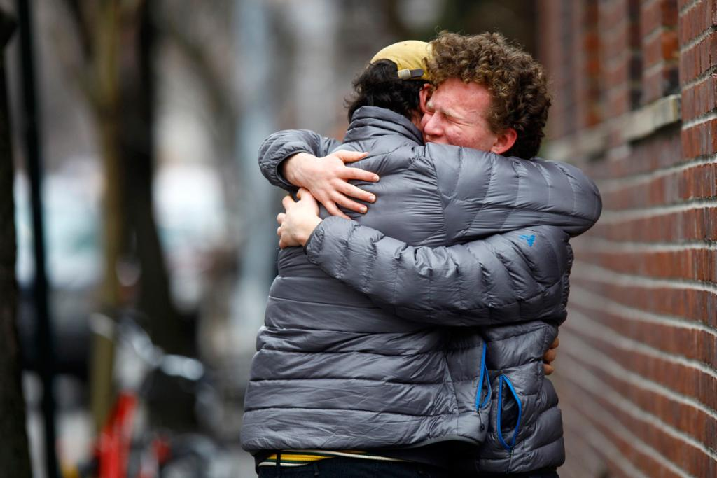 Two men embrace near the apartment where movie actor Philip Seymour Hoffman was found dead in New York.