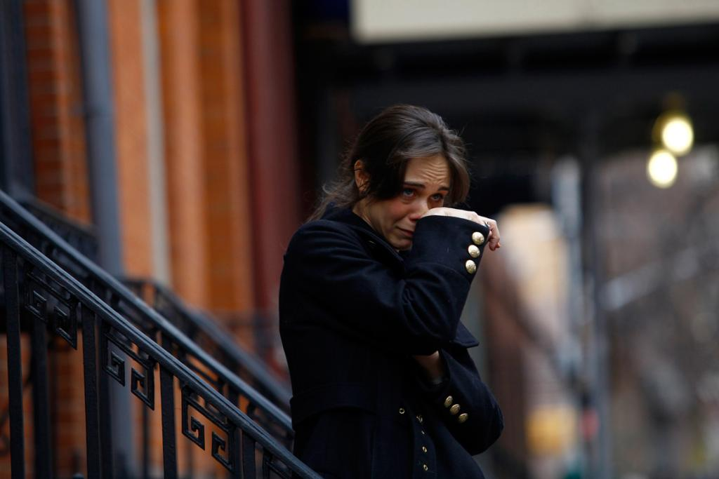 A woman - who declined to give her name and said she was friends and working on a project with movie actor Philip Seymour Hoffman - wipes away tears as she stands across the street from the apartment where they found the celebrity dead.