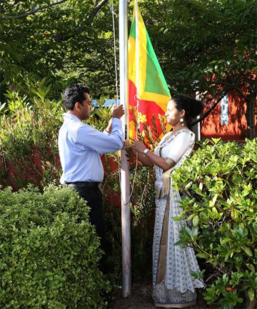 Nithi Rajakafunanayake, left, and Upeksha Padmachandra raise the Sri Lankan flag at the Southern Institute of Technology, in Invercargill.