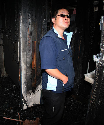 SEAT OF FIRE: Rosedale Chinese Takeaways owner Bruce Kwongassesses the damage at the back of his store after the Salford St shopping centre in Invercargill was damaged by a fire.