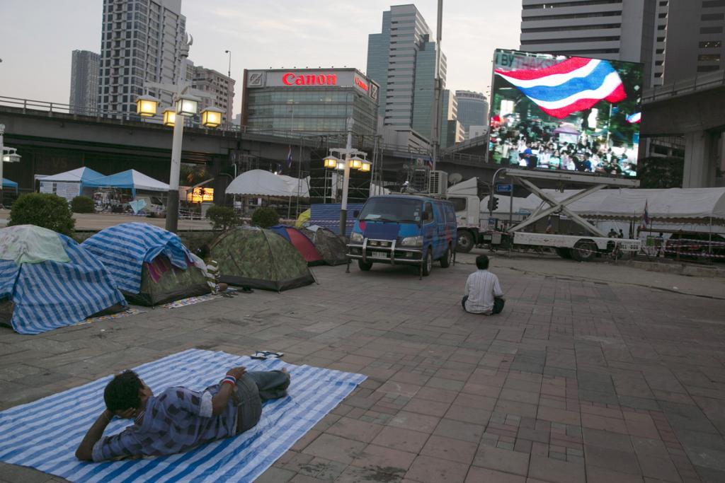 """Anti-government protestors listen to speeches at the Lumpini Park protest site on Tuesday in Bangkok. After disrupting the general election, anti-government demonstrators are continuing their campaign to oust Prime Minister Yingluck Shinawatra and the three-week-old """"Bangkok Shutdown"""" has blocked major intersections."""