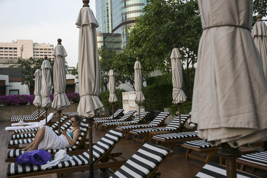 A lone woman sits at a pool at a five-star hotel near a major protest site February 4 in Bangkok. Business has reportedly suffered and hotels are dealing with major losses as the political turmoil continues without any end in sight.