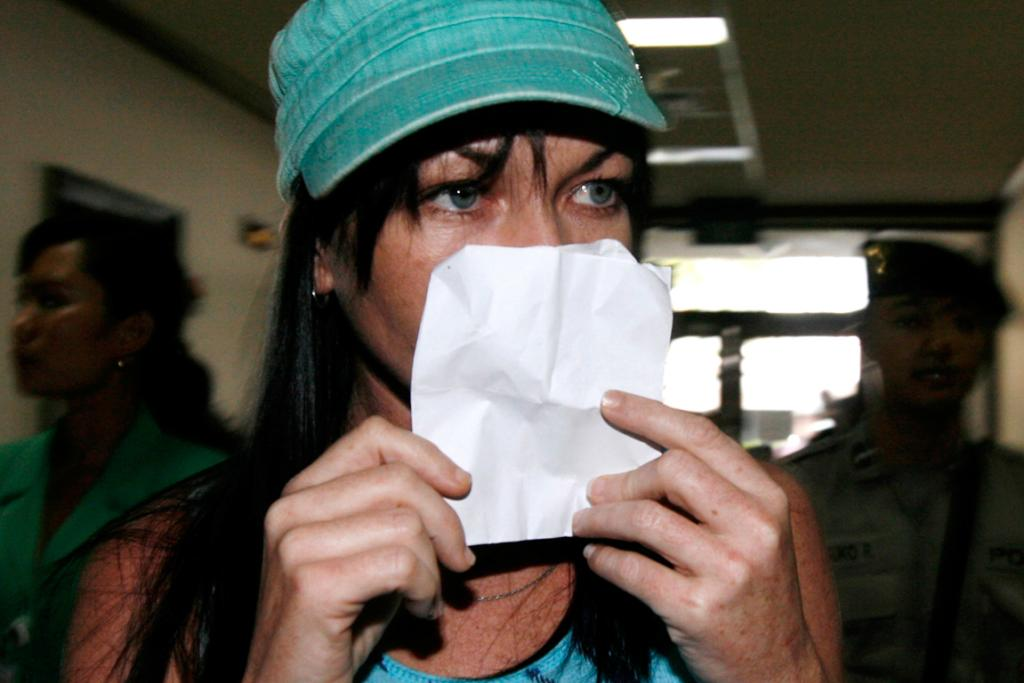 Convicted Australian drug trafficker Schapelle Corby covers her face as she is escorted by policeman while leaving a beauty salon near Sanglah hospital in Indonesia's island of Bali in July 2008.
