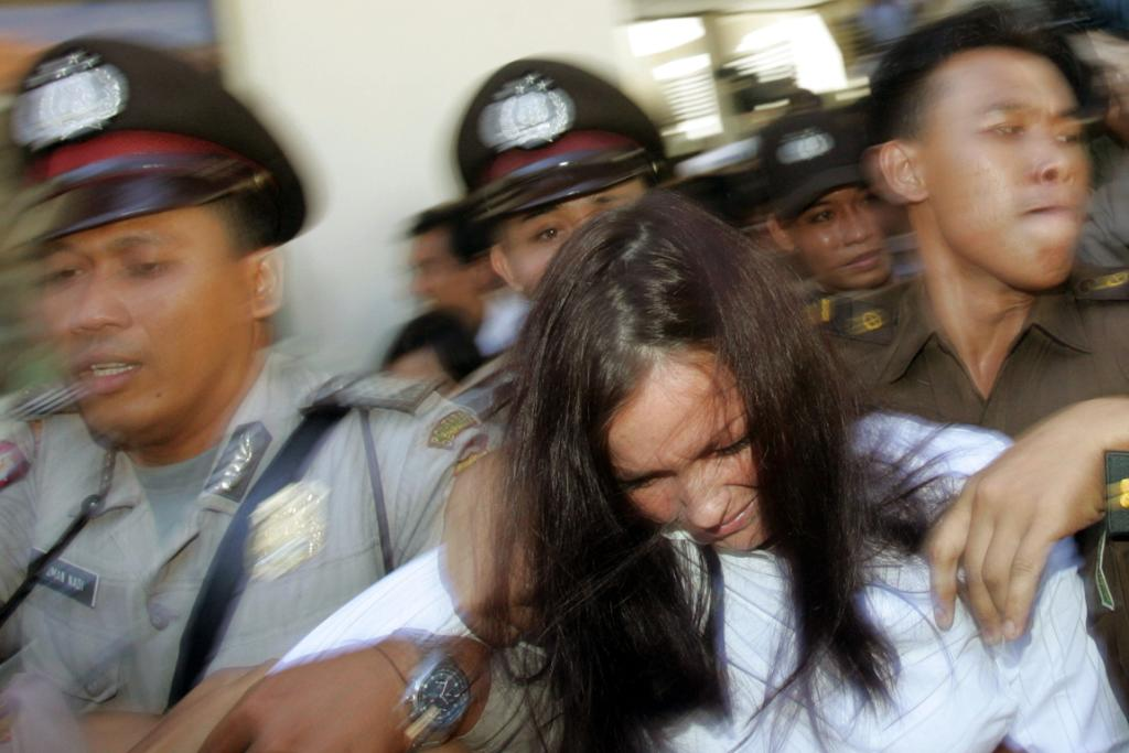 Australian beauty therapist Schapelle Corby is escorted by police after she arrived at a Denpasar court on the Indonesian resort island of Bali July 20, 2005.