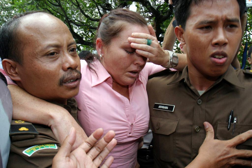 Australian Schapelle Corby is escorted by court officials as she leaves a Denpasar courtroom during her trial on the Indonesian resort island of Bali April 14, 2005.