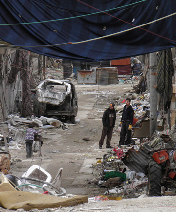 WAR ZONE: Residents stand along a damaged street filled with debris in the besieged area of Homs.