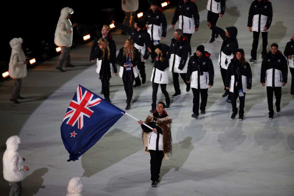 Flagbearer Shane Dobbin leads the New Zealand team into the Olympic stadium.