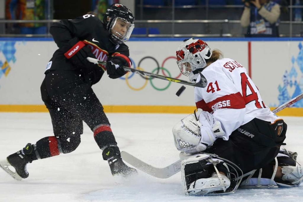 Canada's Jayna Hefford shoots on Switzerland's Florence Schelling during their women's ice hockey group game.