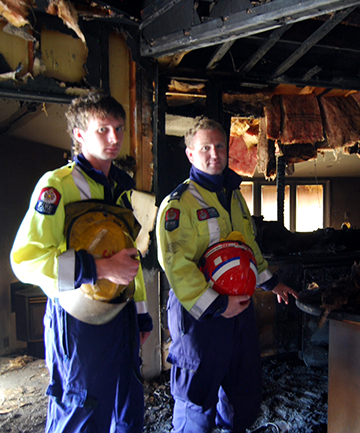 UP IN SMOKE: Alexandra firefighter Nathan Mawhinney, left, and station officer Shane Ryan inspect the devastation caused by a fire in an Alexandra house on Friday night.