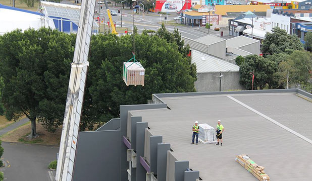 FEEL THE POWER: Solar panels are lifted on to the roof of the PNCC building.