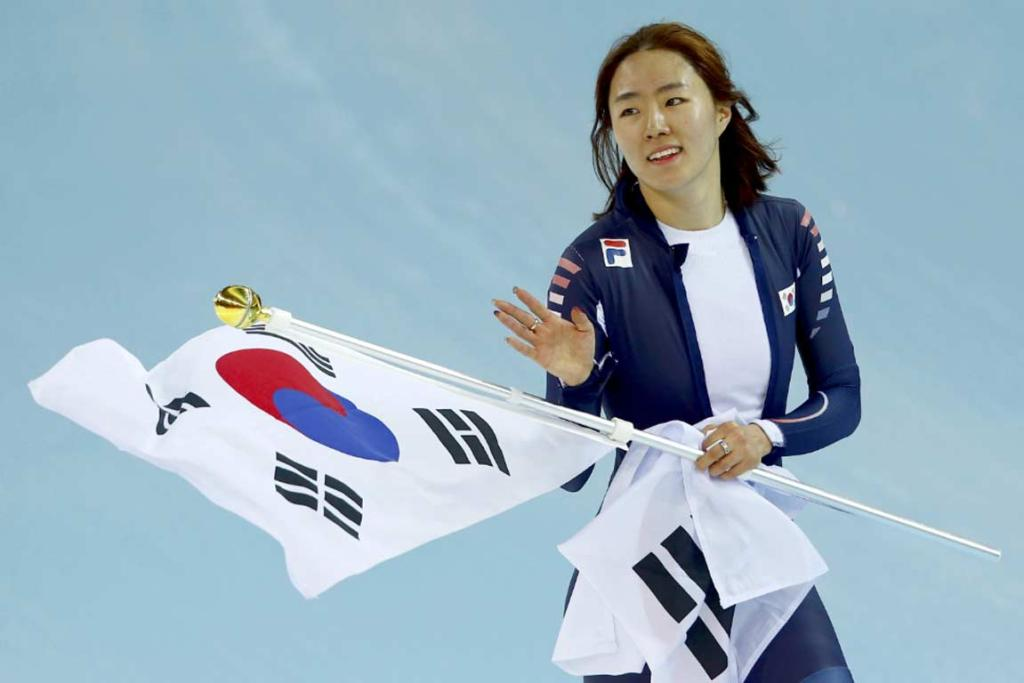 Lee Sang-hwa skates a victory lap with the South Korean flag after blitzing the Olympic record to win the women's 500m.