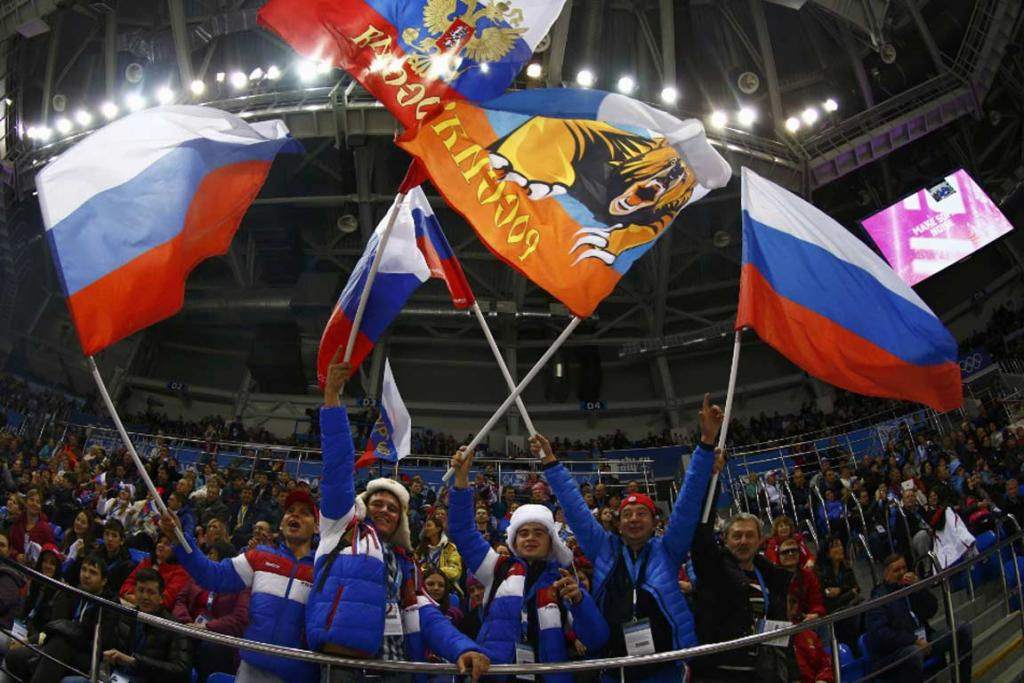 Russian ice hockey fans wave flags during a game between Sweden and Germany.