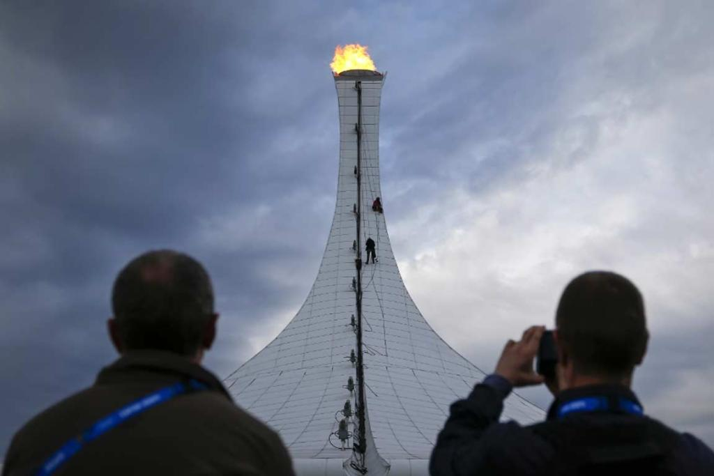 Tourists watch as workers repel down the Olympic flame structure in Sochi.