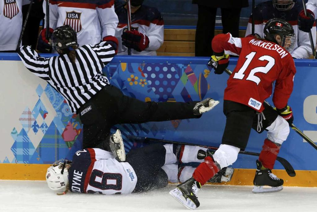 A referee falls on Team USA's Kendall Coyne after she collided with Canada's Meaghan Mikkelson during the first period of their women's ice hockey game.