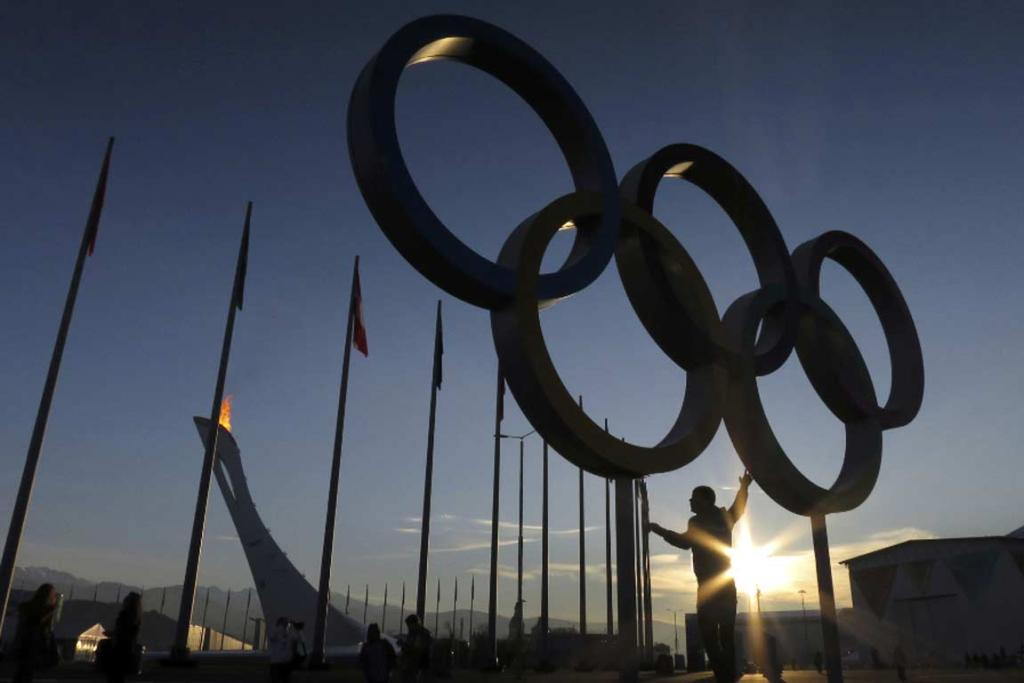 A tourist poses under a set of Olympic rings as the sun rises on the Sochi Olympic Park.