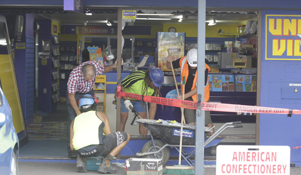 Repair work is carried out on the United Video store at the Glenview Shopping Centre after a car smashed through the front window.