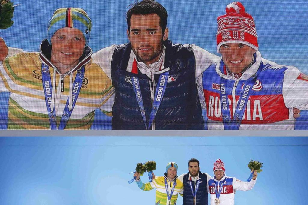 France's Martin Fourcade (centre) on the medal dais for the men's biathlon 20km individual event.